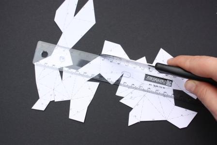 Um die Teile an ihren gestrichelten Linien knicken zu können, nehmt ihr ein Messer und Lineal und drückt die Falzstelle ein.