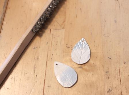 Die gebrannten Blätter, während des Reinigungsprozesses. Das Silber kommt unter dem Weiß zum Vorschein.